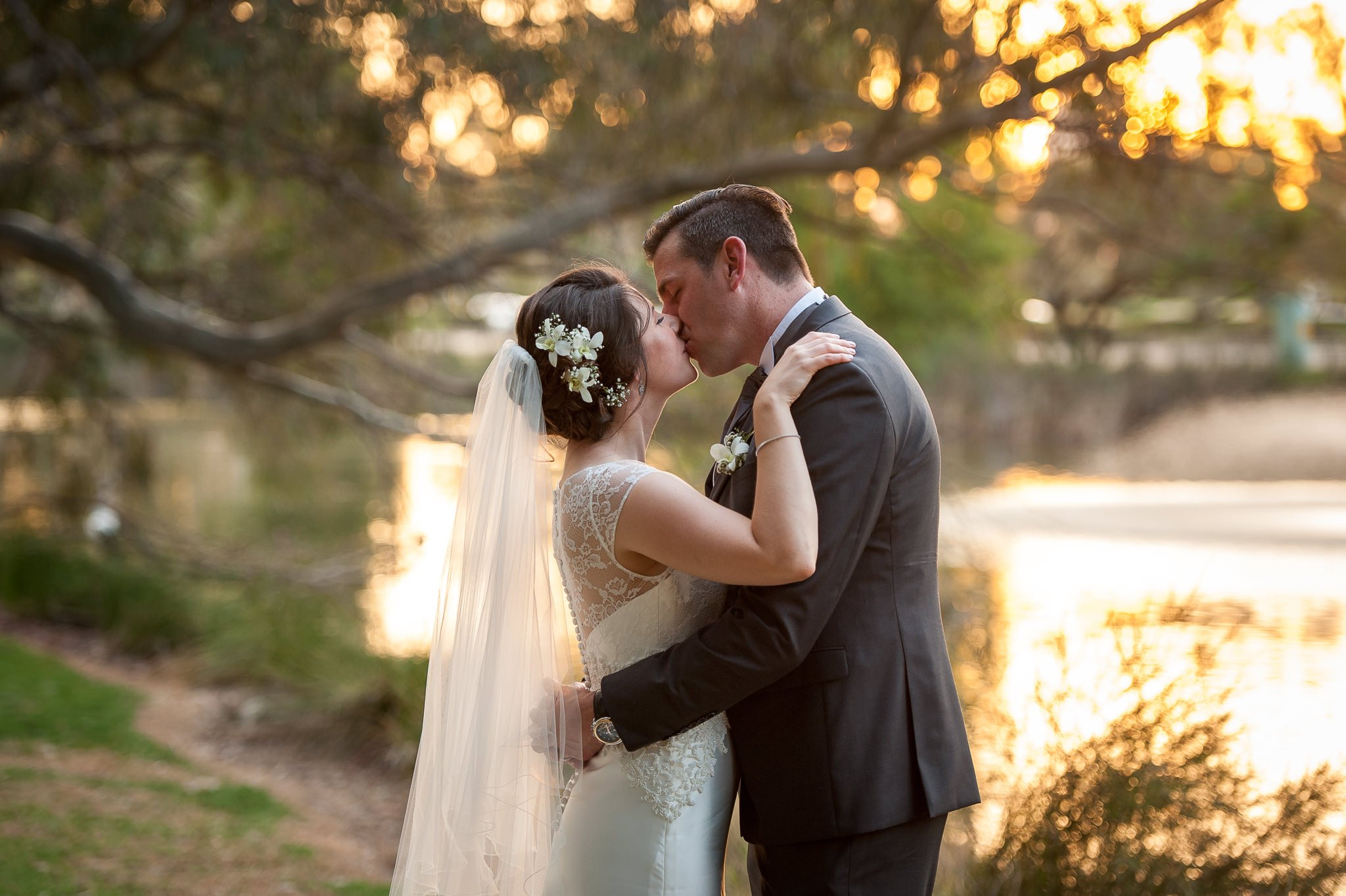 bride and groom by a lake in last light