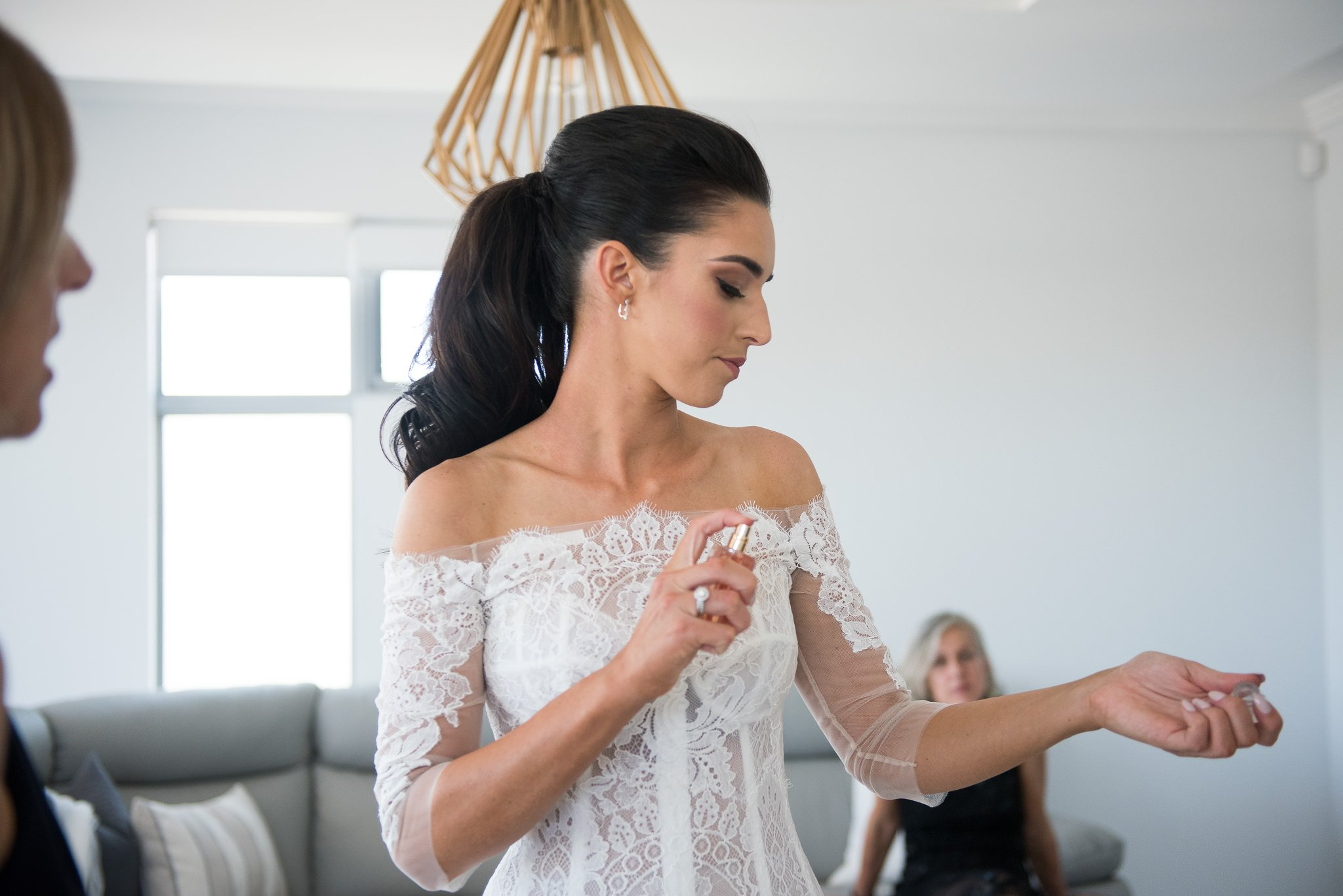 bride putting perfume on