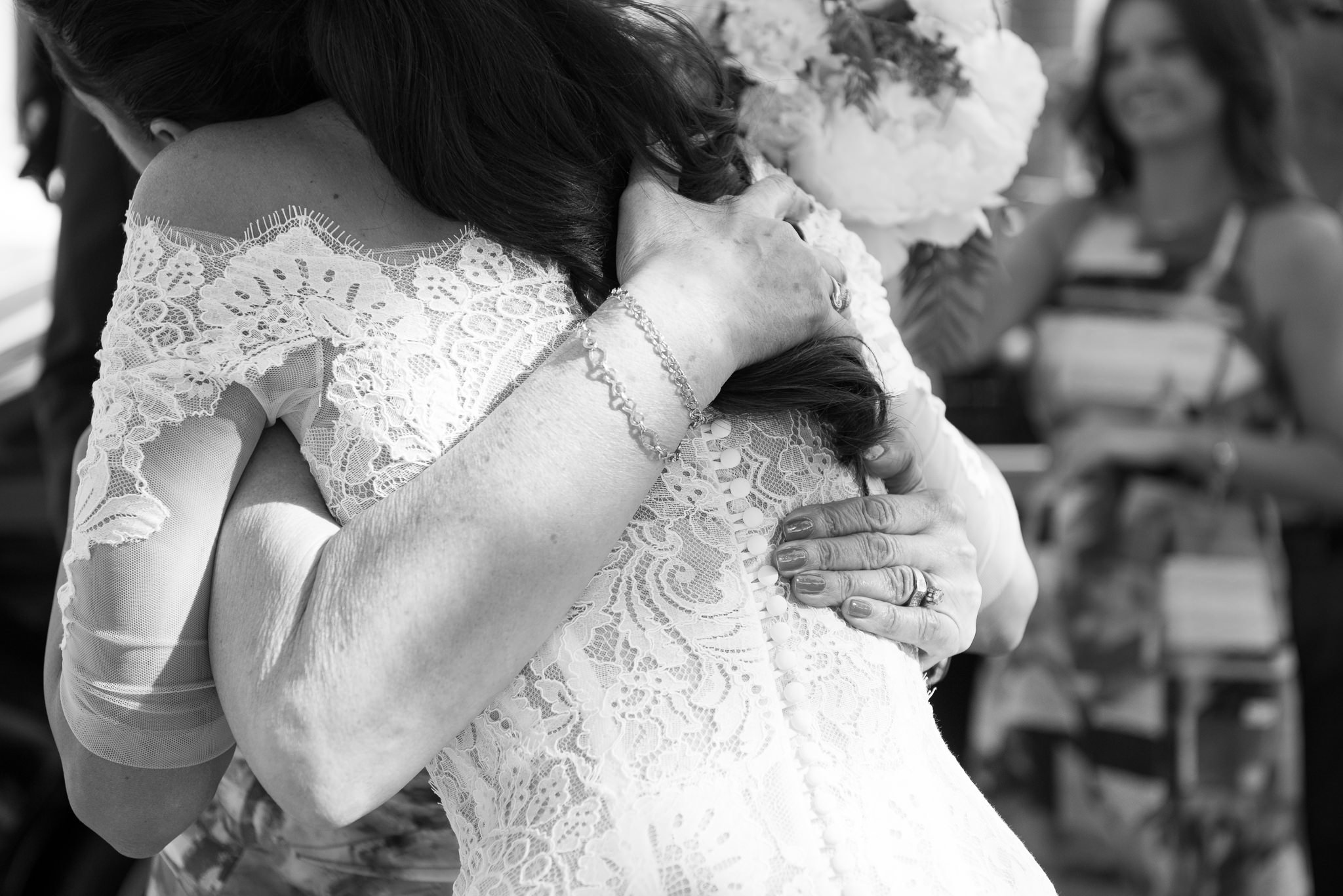bride getting hug from mother in law