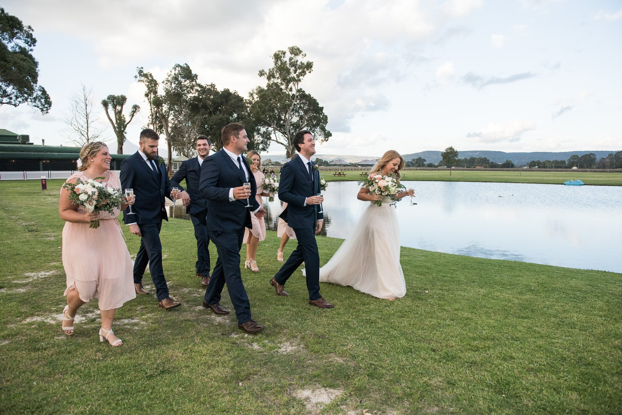 bridal party walking by a lake