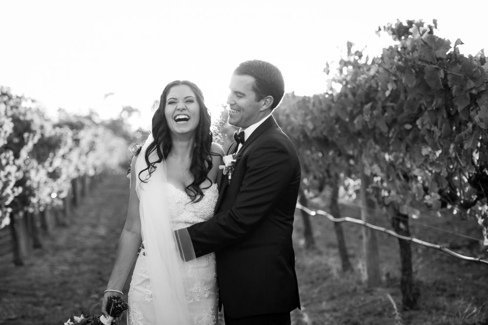 bride and groom laughing in the vinyard