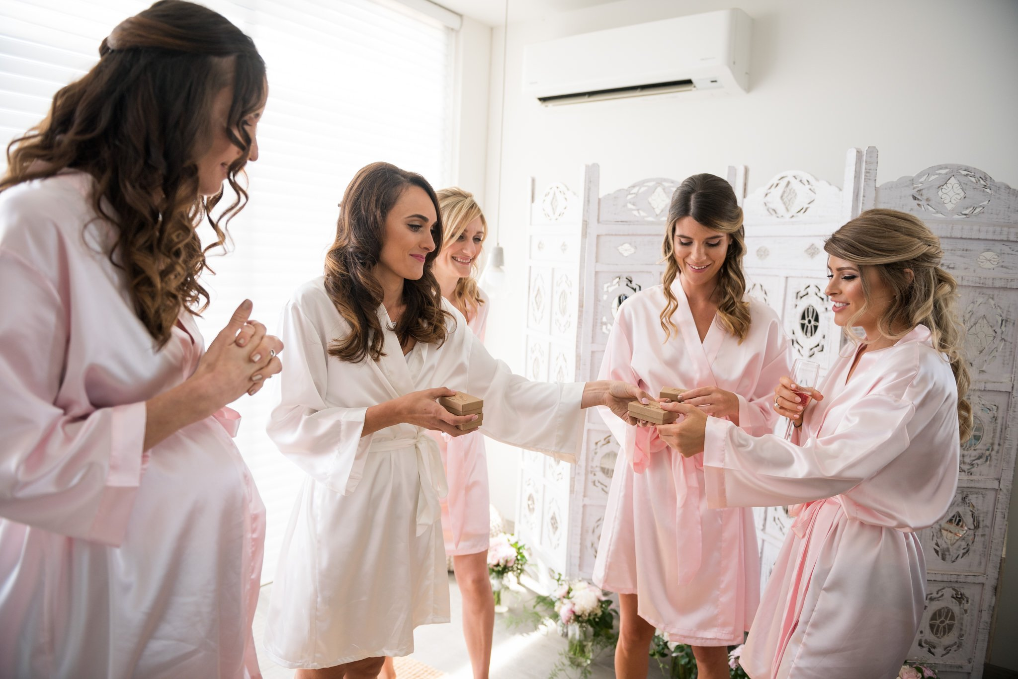 bride handing out gifts to bridesmaids