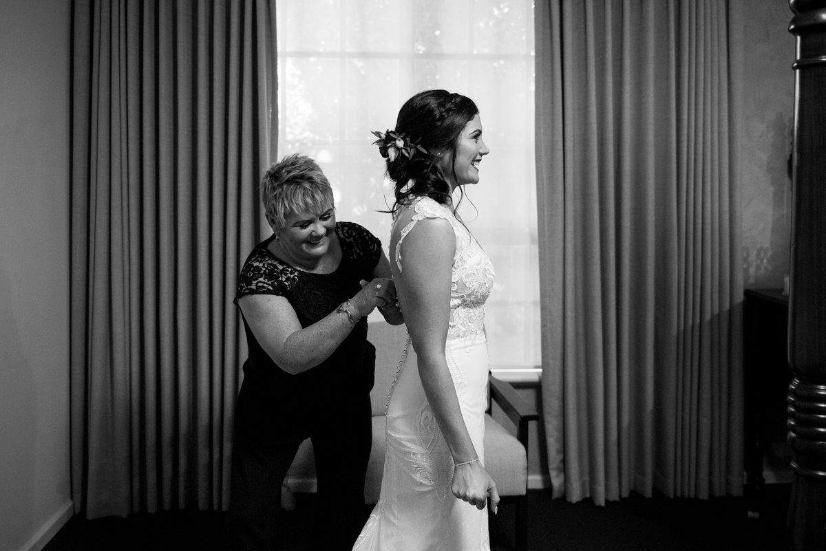 mother of the bride buttoning her dress