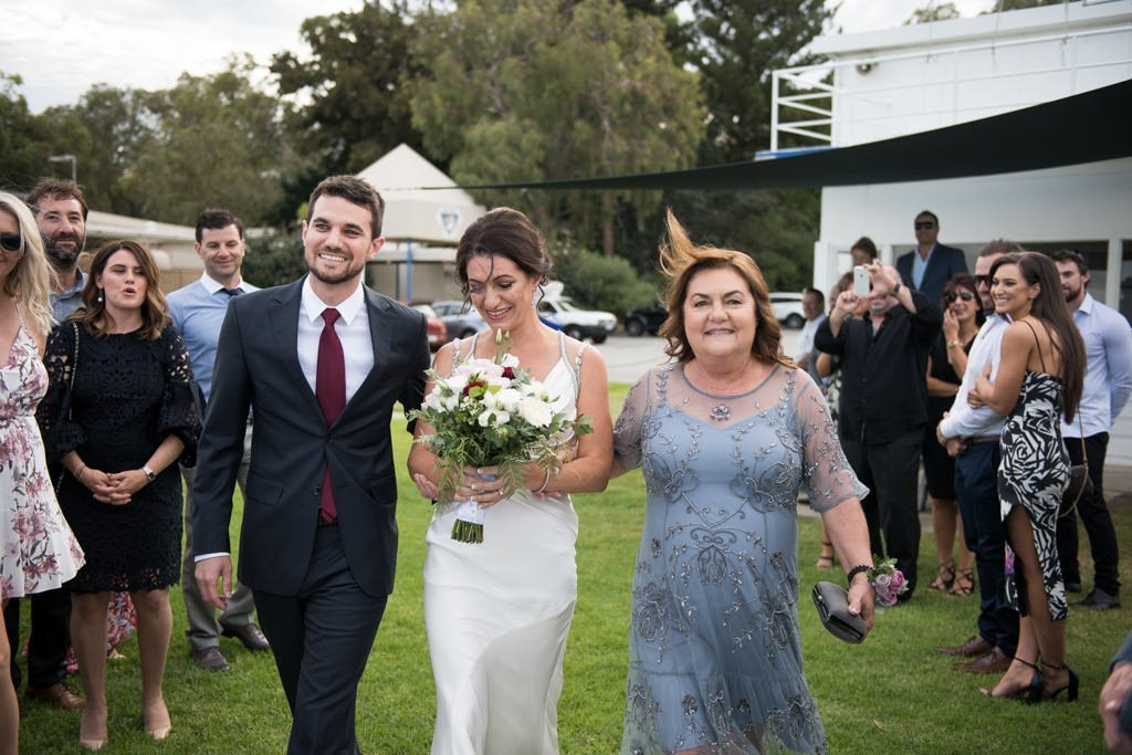 bride walking down the aisle with her mum and brother